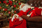 Santa Clause snoozing in a decorated living room with sack full poster