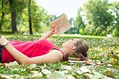 young woman relaxing and reading book poster