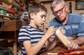 grandfather with grandson in the carpentry workshop. boy learns carpentry skills poster