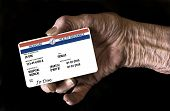 An elderly female hand holds a mock United State government Medicare Health Insurance card. It is a generic card. This is a photo illustration. poster