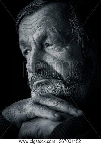 Pensive elderly bearded man black and white portrait