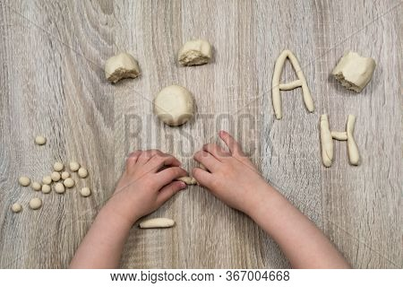 Childrens Hands Fly Figures Of Salt Dough, Clay, Plasticine On A Wooden Background. Childrens Creati