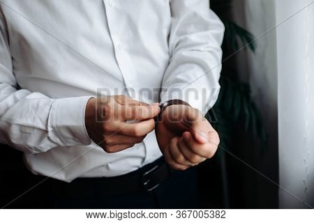 A Sexy Male Businessman Fastens A Cufflink On His Wrist Watch, The Cuff Of The Sleeve Of A Luxurious