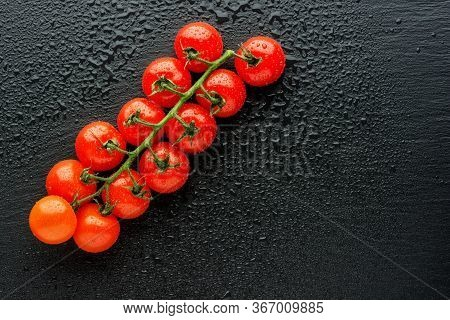 Fresh Cherry Tomatoes On A Black Background With Water Drops. Top View Or Flat Lay. Minimal Black St