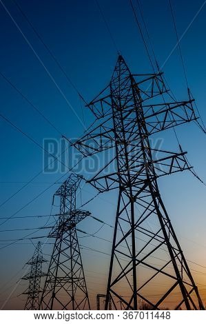 Electric Post With Wires With Sunset Background. Transmission Tower. Power Lines On A Colorful Sunse