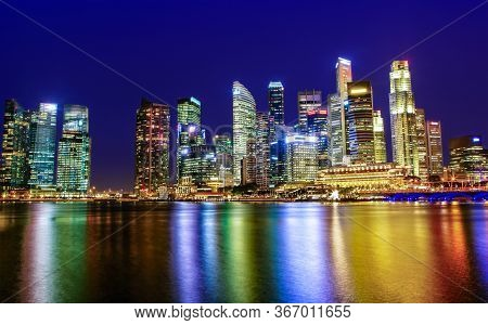 Singapore Skyline Of Downtown City Business District At Twilight Blue Hour With Colorful Reflections