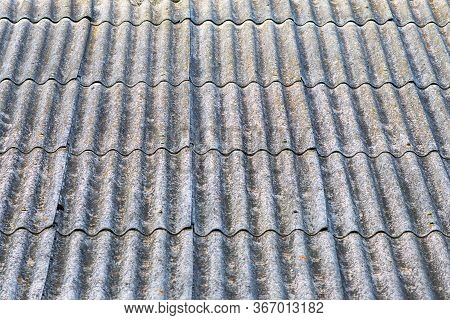 Close-up View Of Old Wavy Slate Roof With Moss. Texture Of Old Slate With Moss. Shed Roof Covered Wi