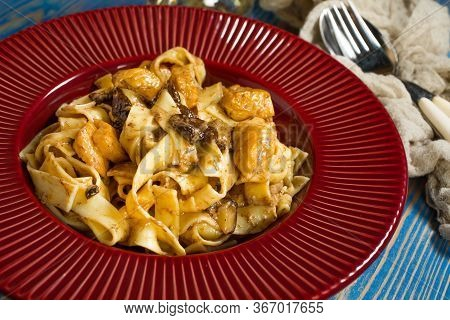 Tagliatelle Pasta With Chicken And Boletus Mushrooms On A Plate.