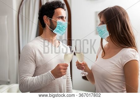 Man and Woman hands toasting with Champagne wearing a mask, coronavirus concept