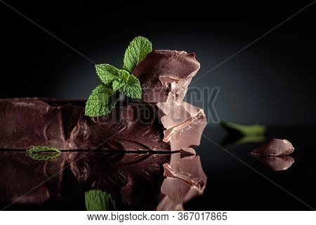 Large Piece Of Dark Bitter Chocolate With Mint On A Black Reflective Background. Copy Space.