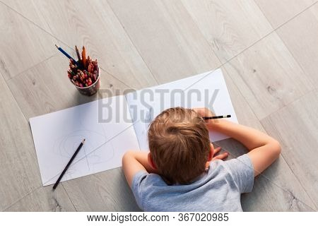 Little Boy Drawing On The Floor In His Room