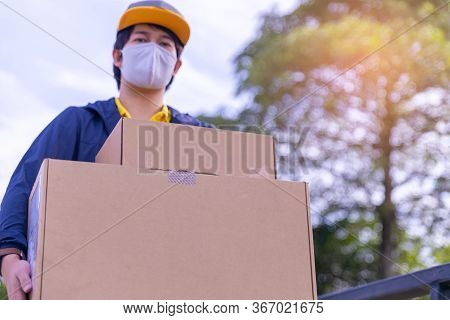 Blur Delivery Man Employee Wearing A Face Mask And Holding Boxes Outside, Service Quarantine Pandemi