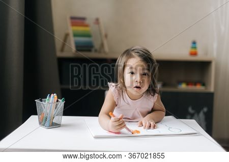 Surprised Little Two-year-old Girl Wearing Casual White Dress Is Drawing On White Paper With Colorfu