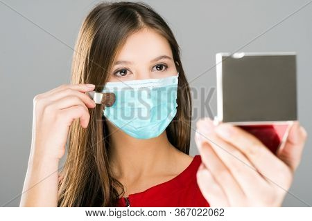 Woman applying makeup and looking in a mirror while wearing mask, funny coronavirus concept