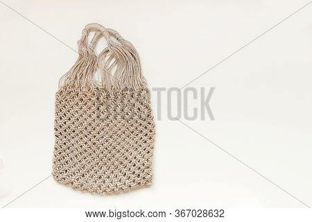 Reusable Net Bag Or Mesh Shopper On Beige Background With Copy Space. Zero Waste, Plastic Free Conce