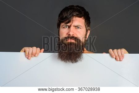 Serious Man With Blank Board. Advertising Banner. Ready For Your Text. Handsome Man Shows Empty Boar