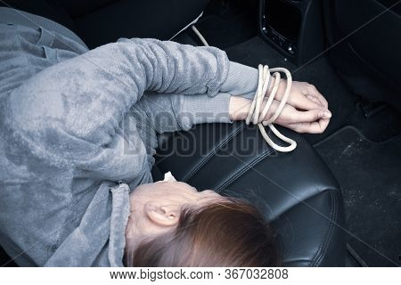Kidnapping. Related Woman Laying In The Car. The Trafficking Of Women. Hands Bound The Prisoner. Unl