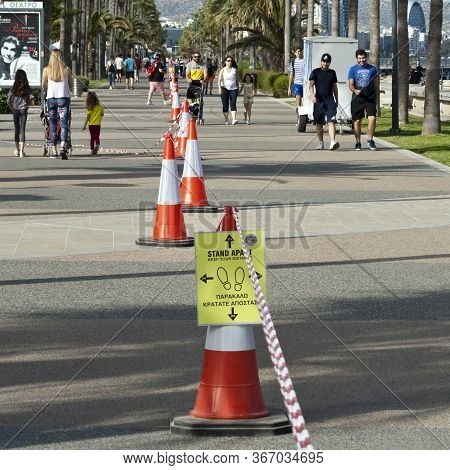 Limassol, Cyprus, May 13th, 2020: Seafront Promenade Molos With People Walking Along Traffic Cones W