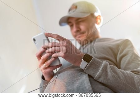 Close Up Young Caucasian Man In Baseball Cap Looking And Using Mobile Smart Phone At Home. Facetime