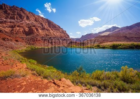 Smooth turn of the Colorado River. Steep river banks of red sandstone. Lee's Ferry is a historic boat ferry. Amazing wildlife. USA. The concept of active, extreme and photo tourism