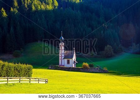 Tyrol, Italy. The Val di Funes Valley. Majestic Dolomites. Small white church with a bell among green lawns on the sunset. The concept of active, ecological and photo tourism