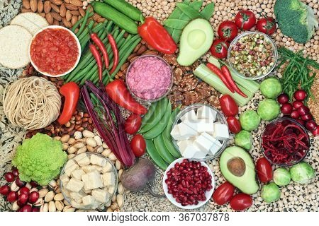 Vegan food for a healthy planet concept with foods high in protein, vitamins, minerals, anthocyanins, antioxidants, omega 3, lycopene, smart carbs and dietary fibre. Healthy ethical eating concept.