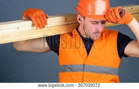Carpenter, Woodworker, Strong Builder On Busy Face Carries Wooden Beam On Shoulder. Man In Protectiv