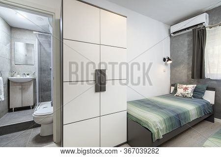 St Julians, Malta - April 28th 2020: Small Twin Bedroom With Turqoise Green Bedding And A Tiny Grey