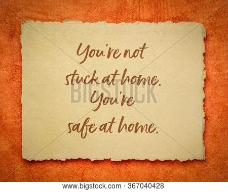 you are not stuck at home, you are safe at home - inspirational note on a handmade rag paper, reminder for self isolation or qurantine during coronavirus pandemic