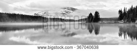 Two Jack lake with snow mountain and water reflection panorama in Banff National Park in Canada.