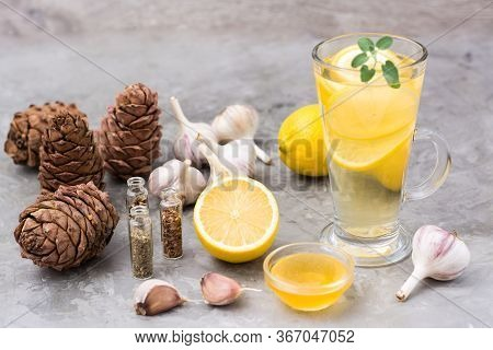 Set Of Natural Antiviral Agents: Lemon, Garlic, Honey, Herbs, Cedar Resin On The Gray Table. Alterna