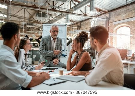 Business Meeting. Mature Businessman Explaining Something To His Colleagues While Sitting At The Off