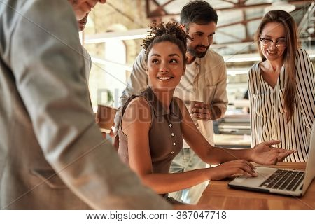 Working Together. Young And Cheerful Afro American Woman Using Laptop And Discussing Something With