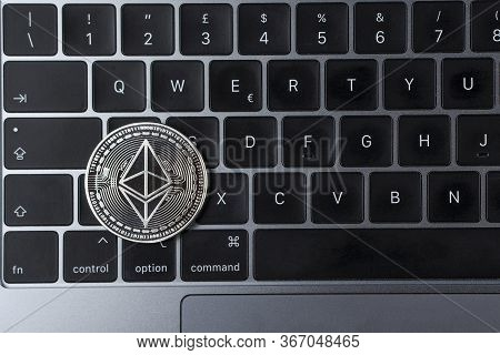 Ethereum Cryptocurrency Crypto Currency. Silver Ethereum Coin With Gold Ethereum Symbol On A Laptop
