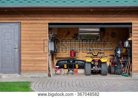 Facade Front View Open Door Atv Quad Bike Motorcycle Parking Messy Garage Building With Wooden Sidin