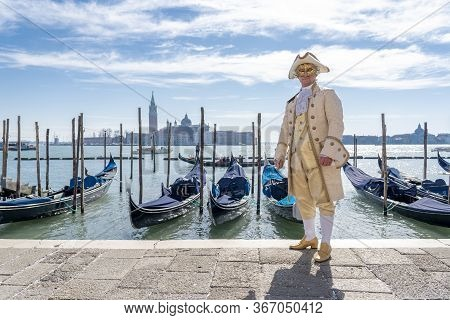 Venetian Masked Model From The Venice Carnival 2016 With Gondolas In The Background. Venice Carnival