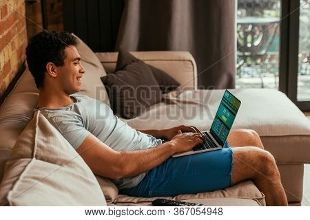 Happy Mixed Race Man Chilling And Using Laptop With Sportsbet Website On Screen During Self Isolatio