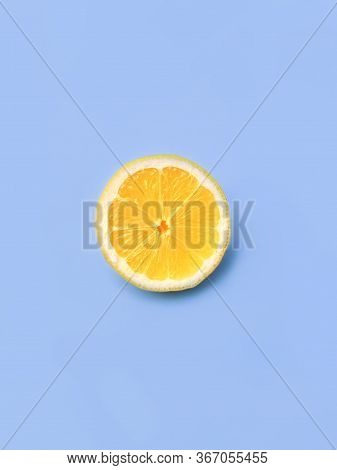 Lemon Slice, Clipping Path, Isolated On A Blue Background, Top View Of Textured Ripe Slice Of Lemon