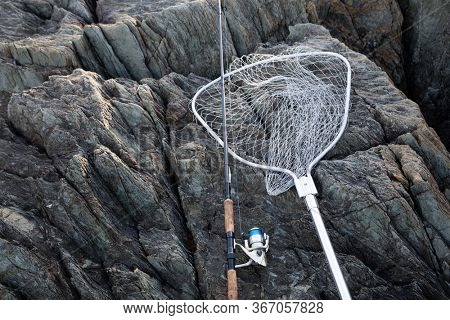 Spinning and landing net on a rocky seashore