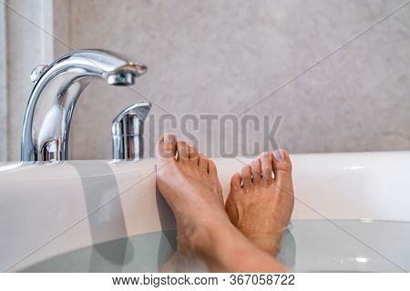 Woman taking a hot bath at luxury hotel - spa wellness body care relaxation. Closeup of happy feet.