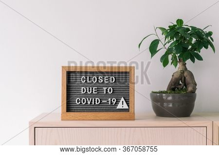 Closed business store due to COVID-19. Coronavirus lifestyle background with message sign at store front counter for closure of businesses and retail shops.
