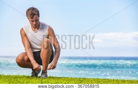 Exercise fitness man getting ready to run walk tying running shoes healthy active outdoor lifestyle walking at beach.