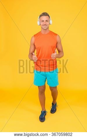 Promoting Healthy Lifestyle. Happy Athlete In Earphones Give Thumbs Ups Yellow Background. Approving