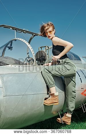 Portrait of a beautiful girl pilot repairing her fighter airplane at the airfield.