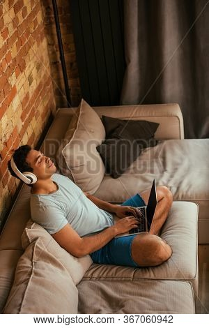 Young Mixed Race Man With Closed Eyes Chilling And Listening Music With Headphones And Laptop On Sof