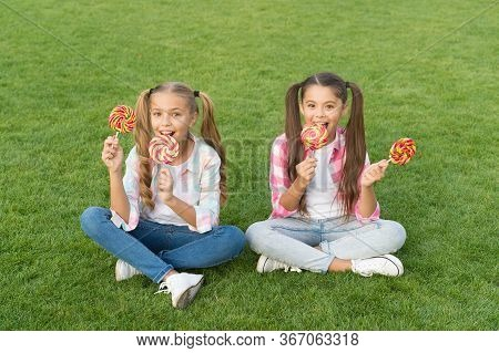 Sweet Caramel. Happy Children Hold Candy Sit Grass. Candy Shop. Lollipop Treats. Candy Means Happine