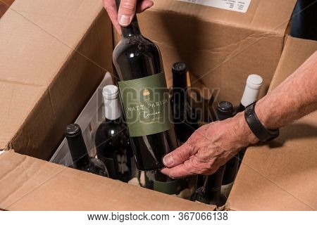 Morgantown, Wv - 19 May 2020: Senior Man Looking At Wine Bottle From Matt Parish Out Of Box Delivere