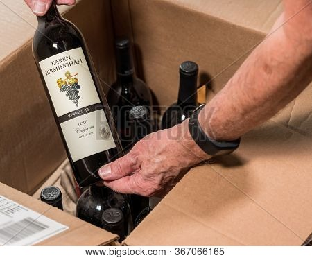 Morgantown, Wv - 19 May 2020: Senior Man Looking At Wine Bottle From Karen Birmingham Out Of Box Del