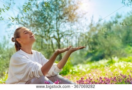Nice happy woman sitting on flowers meadow in the garden, enjoying bright spring sunshine, active spring holidays in countryside