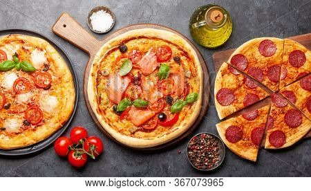 Various tasty homemade pizza with garden tomatoes, cheese, salami and salmon. Top view closeup
